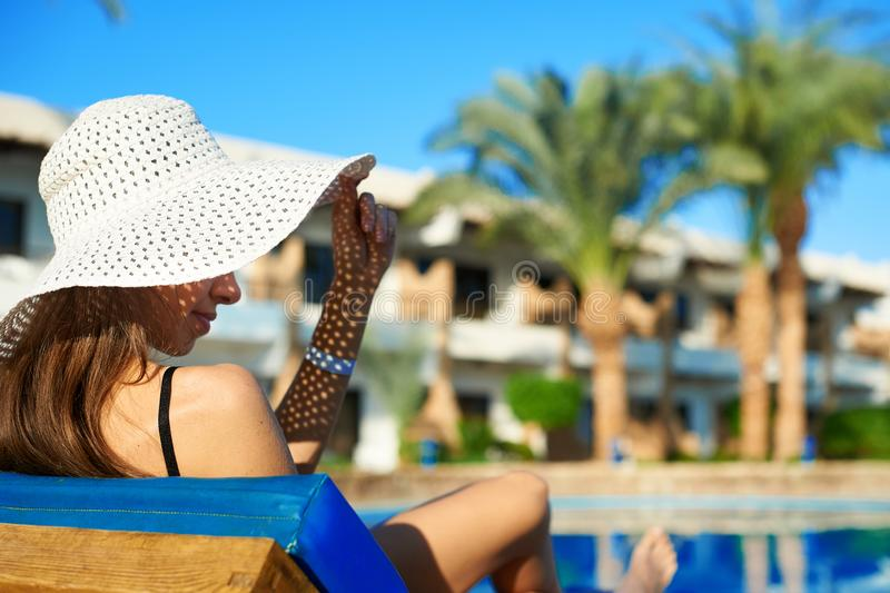 Γυναίκα στο μεγάλο άσπρο καπέλο που βρίσκεται σε έναν αργόσχολο κοντά στην πισίνα στο ξενοδοχείο, θερινός χρόνος έννοιας να ταξιδ στοκ φωτογραφίες με δικαίωμα ελεύθερης χρήσης