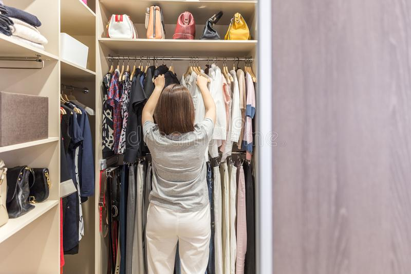 Γυναίκα στο μεγάλο εισαγώμενο ντουλάπι που επιλέγει τα ενδύματα σύγχρονα ντουλάπα και βεστιάριο με το διάστημα αντιγράφων στοκ φωτογραφία