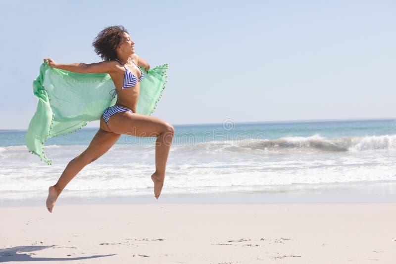 Γυναίκα στο μπικίνι με το μαντίλι που πηδά στην παραλία στοκ εικόνα με δικαίωμα ελεύθερης χρήσης