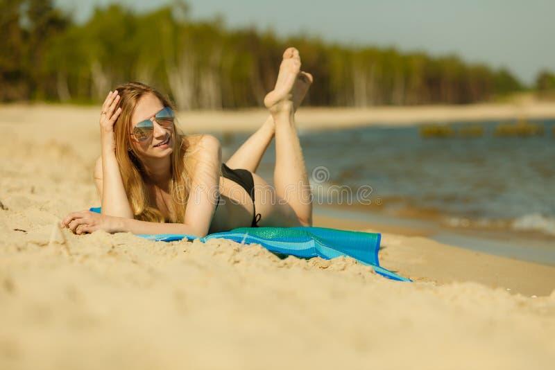 Γυναίκα στο μπικίνι που κάνει ηλιοθεραπεία και που χαλαρώνει στην παραλία στοκ εικόνες