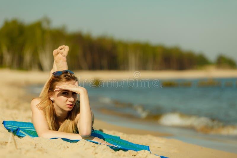 Γυναίκα στο μπικίνι που κάνει ηλιοθεραπεία και που χαλαρώνει στην παραλία στοκ εικόνες με δικαίωμα ελεύθερης χρήσης
