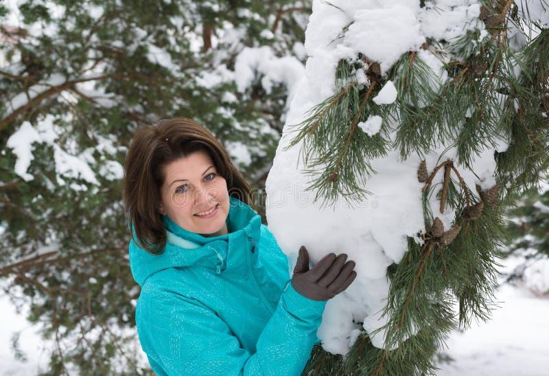 Γυναίκα στο μπλε αθλητικό σακάκι στο δάσος χειμερινών πεύκων στοκ φωτογραφία