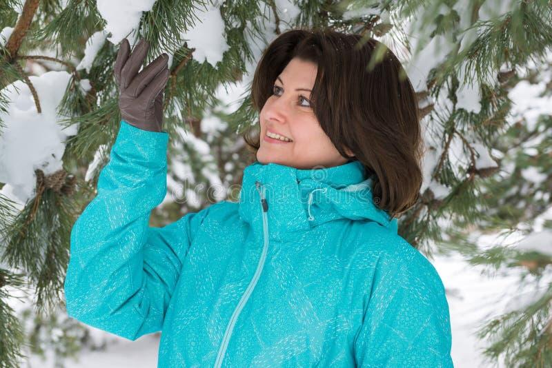 Γυναίκα στο μπλε αθλητικό σακάκι στο δάσος χειμερινών πεύκων στοκ φωτογραφία με δικαίωμα ελεύθερης χρήσης