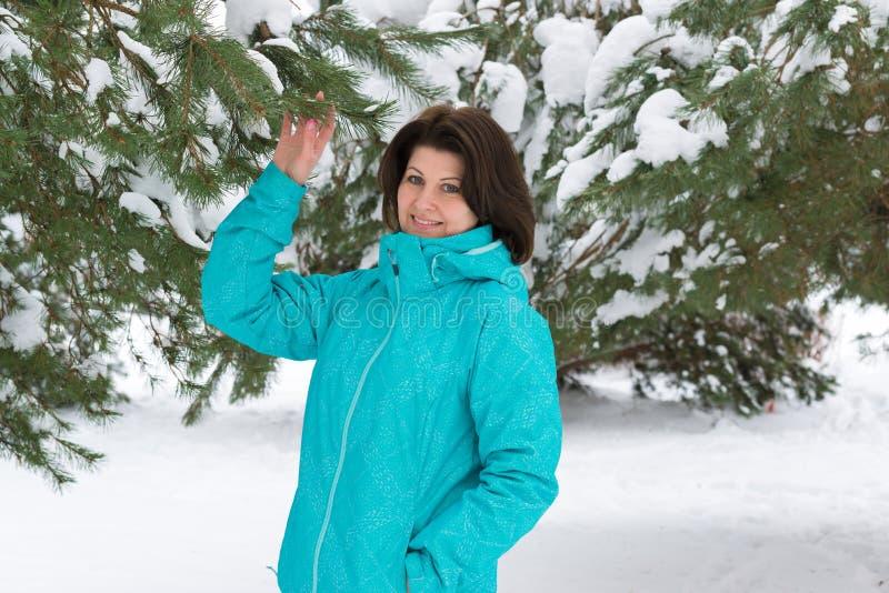 Γυναίκα στο μπλε αθλητικό σακάκι στο χιονισμένο δάσος έλατου στοκ εικόνα με δικαίωμα ελεύθερης χρήσης