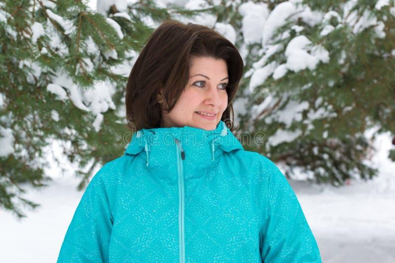 Γυναίκα στο μπλε αθλητικό σακάκι στο χιονισμένο δάσος έλατου στοκ εικόνες με δικαίωμα ελεύθερης χρήσης