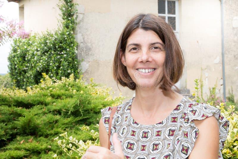 Γυναίκα στο μπροστινό παλαιό χαμόγελο σπιτιών κήπων και ευτυχής στοκ εικόνες