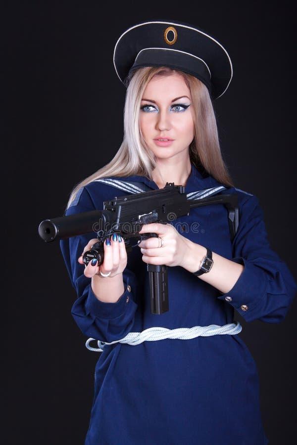 Γυναίκα στο ναυτικό ομοιόμορφο με ένα submachine πυροβόλο όπλο στοκ εικόνα