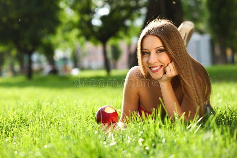 Γυναίκα στο πάρκο με το βιβλίο στοκ φωτογραφίες