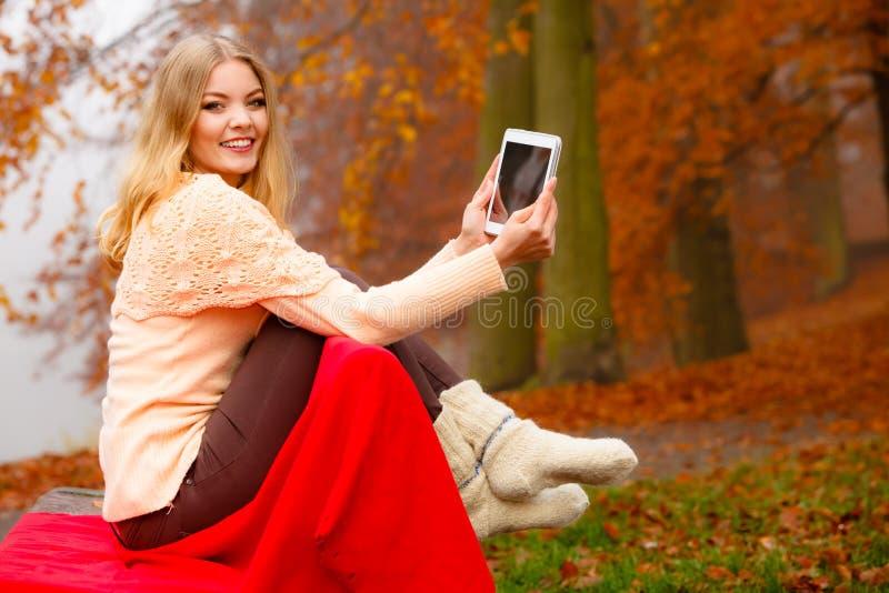 Γυναίκα στο πάρκο φθινοπώρου που χρησιμοποιεί την ταμπλέτα στοκ εικόνες