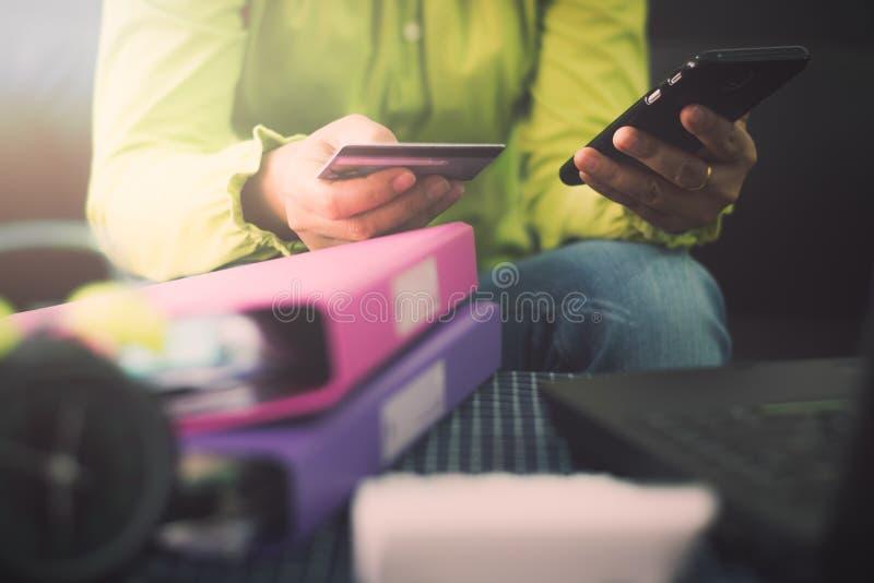Γυναίκα στο περιστασιακό πουκάμισο που πληρώνει με την πιστωτική κάρτα on-line ενώ makin στοκ εικόνα με δικαίωμα ελεύθερης χρήσης