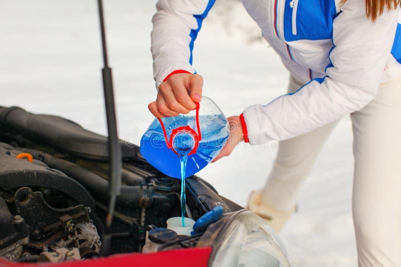 Γυναίκα στο πλύσιμο οθόνης αυτοκινήτων αντιψυκτικού έκχυσης σακακιών σκι στοκ φωτογραφία με δικαίωμα ελεύθερης χρήσης