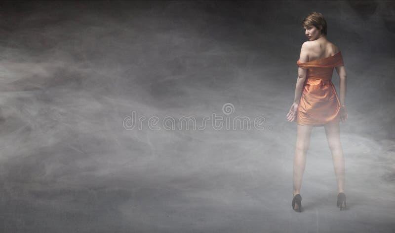 Γυναίκα στο πορτοκαλί φόρεμα στοκ φωτογραφία με δικαίωμα ελεύθερης χρήσης