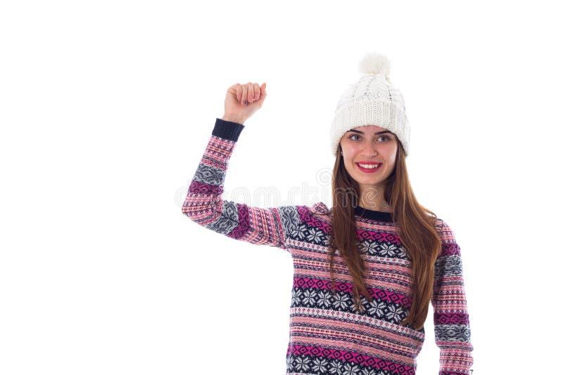 Γυναίκα στο πουλόβερ και το άσπρο καπέλο που παρουσιάζουν πυγμή στοκ φωτογραφίες