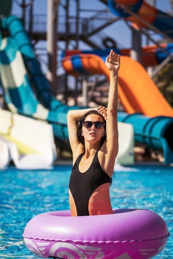 Γυναίκα στο ρόδινο λαστιχένιο δαχτυλίδι στην πισίνα στοκ εικόνες