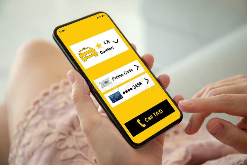 Γυναίκα στο ρόδινο τηλέφωνο εκμετάλλευσης φορεμάτων με app το ταξί στοκ εικόνες