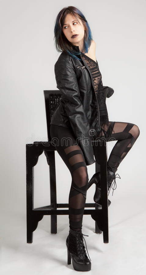 Γυναίκα στο σακάκι δέρματος και περικνημίδες στην έδρα στοκ εικόνα με δικαίωμα ελεύθερης χρήσης