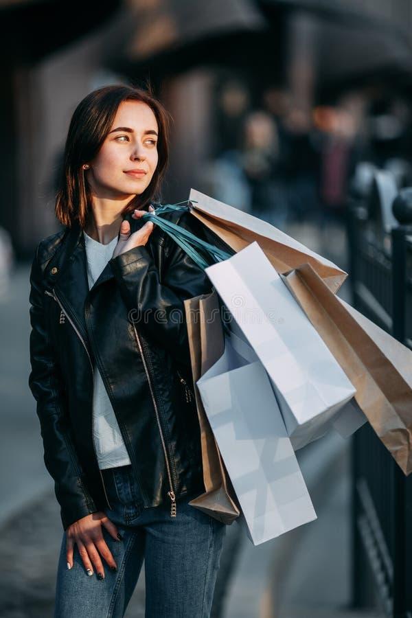 Γυναίκα στο σακάκι δέρματος που φέρνει πολλές τσάντες εγγράφου στοκ φωτογραφία