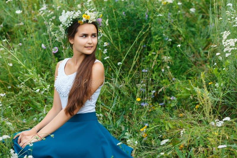 Γυναίκα στο στεφάνι από τα wildflowers που κάθεται στη χλόη στοκ φωτογραφία με δικαίωμα ελεύθερης χρήσης