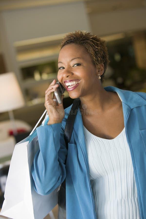 Γυναίκα στο τηλέφωνο κυττάρων στο κατάστημα επίπλων στοκ εικόνες με δικαίωμα ελεύθερης χρήσης