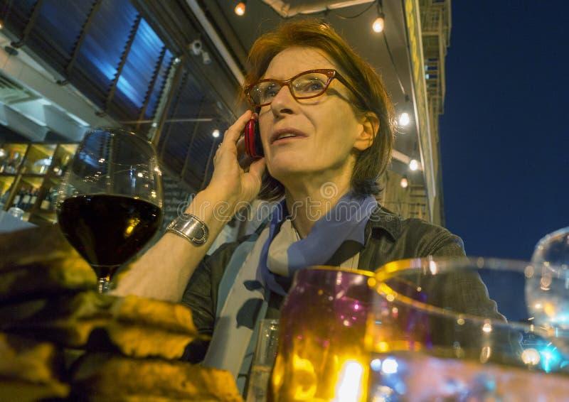Γυναίκα στο τηλέφωνο στο υπαίθριο εστιατόριο στοκ φωτογραφίες