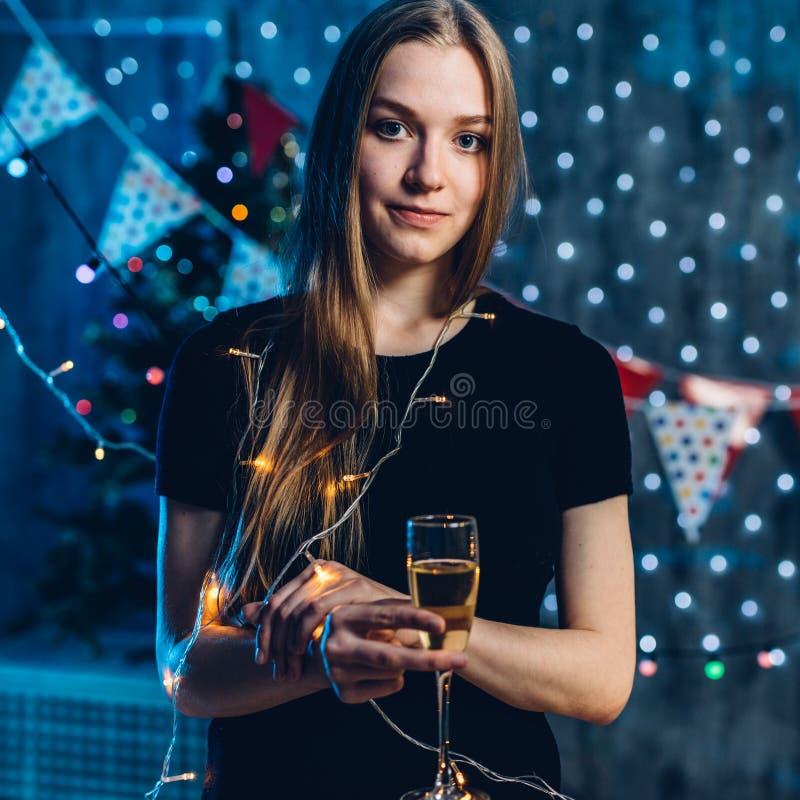 Γυναίκα στο φόρεμα βραδιού με το γυαλί του νέου έτους εορτασμού κρασιού σπινθηρίσματος, Χριστούγεννα στοκ φωτογραφίες