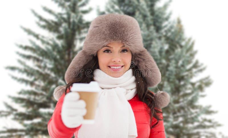 Γυναίκα στο χειμερινό καπέλο γουνών με τον καφέ πέρα από τα δέντρα έλατου στοκ φωτογραφία με δικαίωμα ελεύθερης χρήσης