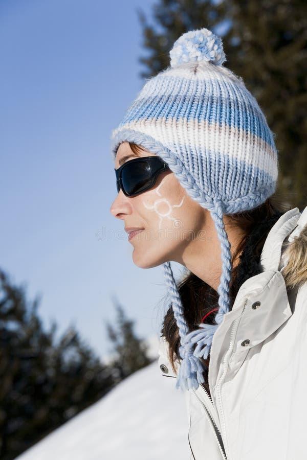 Γυναίκα στο χιόνι με έναν μικρό ήλιο στο μάγουλό της στοκ φωτογραφίες