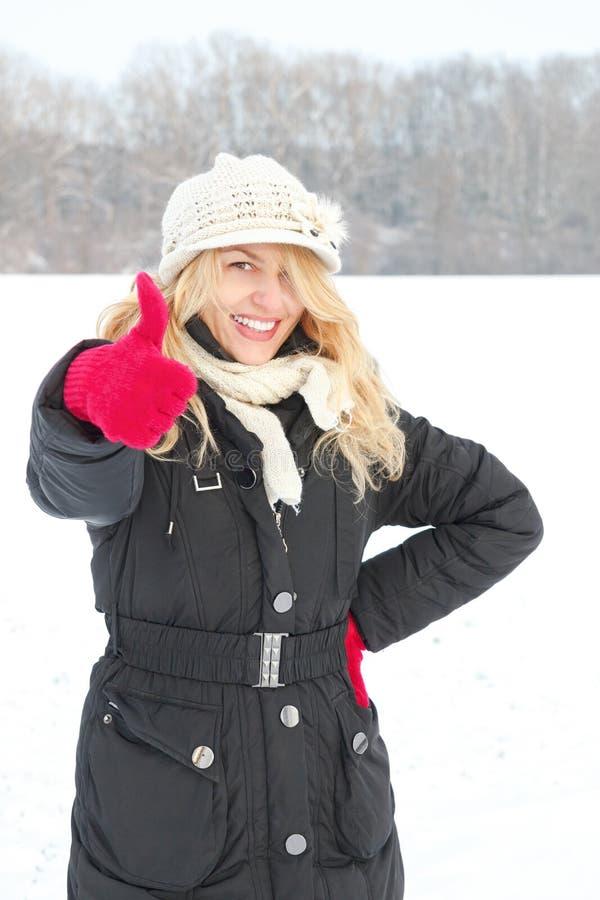 Γυναίκα στο χιόνι που εξετάζει επάνω τη κάμερα με τον αντίχειρα επάνω στο εξωτερικό στοκ εικόνες