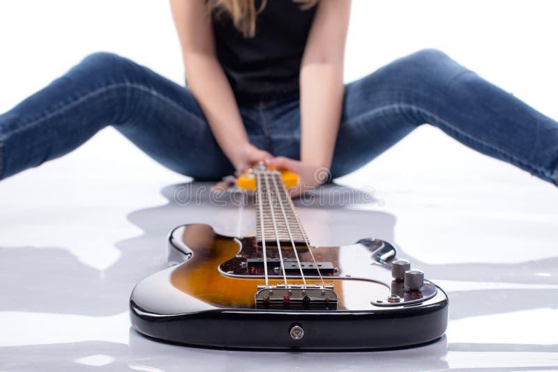 Γυναίκα συνεδρίασης με τη βαθιά κιθάρα στοκ φωτογραφία με δικαίωμα ελεύθερης χρήσης