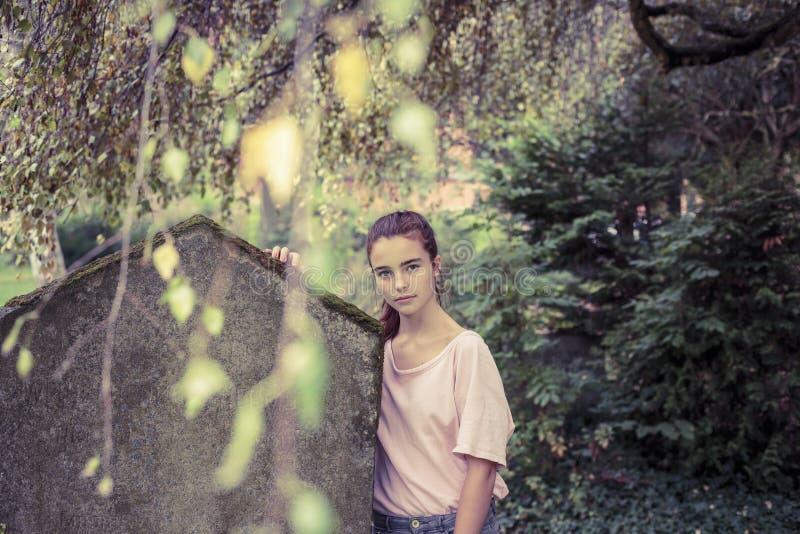 Γυναίκα σχετικά με μια βρύο ταφόπετρα στοκ εικόνες με δικαίωμα ελεύθερης χρήσης