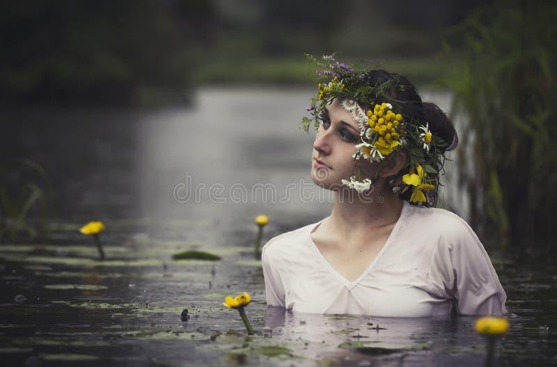 Γυναίκα τέχνης με το στεφάνι στο κεφάλι της σε ένα έλος στα ξύλα Υγρό W στοκ εικόνες