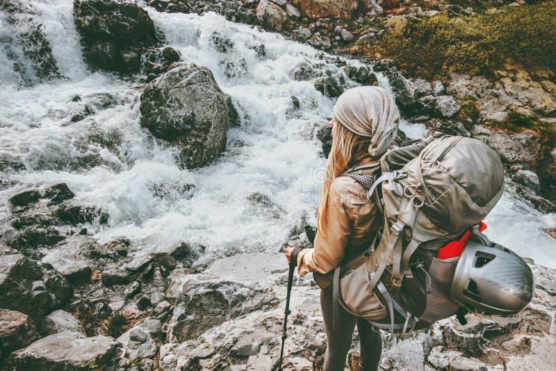Γυναίκα ταξιδιού τυχοδιωκτών που με το σακίδιο πλάτης στον ποταμό στα βουνά στοκ εικόνες