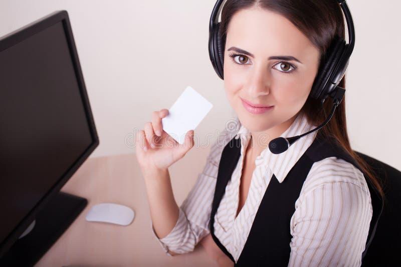 Γυναίκα τηλεφωνικών κέντρων με την κάσκα που παρουσιάζει επαγγελματική κάρτα στοκ εικόνες