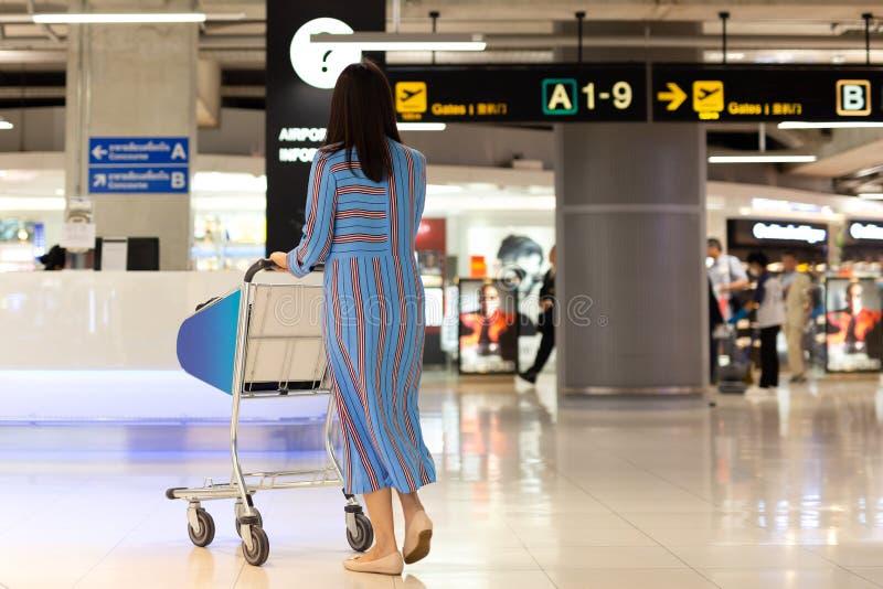Γυναίκα τουριστών στην τελική αναχώρηση έρευνας αερολιμένων με στο κάρρο καροτσακιών στοκ φωτογραφία