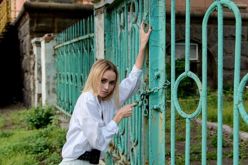 Γυναίκα του βλέμματος μόδας κοντά στην εκλεκτής ποιότητας πύλη r στοκ εικόνα με δικαίωμα ελεύθερης χρήσης