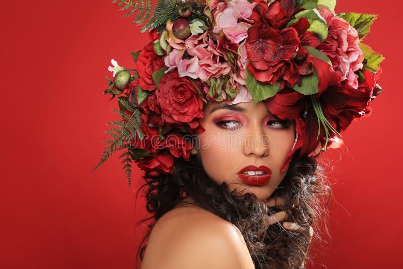 Γυναίκα του Λατίνα με Floral Headpiece στο κόκκινο στοκ εικόνες