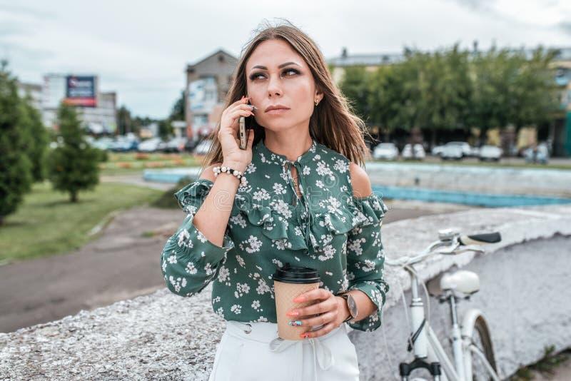Γυναίκα το καλοκαίρι στην πόλη, που καλεί το τηλέφωνο, στο χέρι της ένα τσάι φλιτζανιών του καφέ Ποδήλατο δέντρων υποβάθρου Επιχε στοκ φωτογραφίες