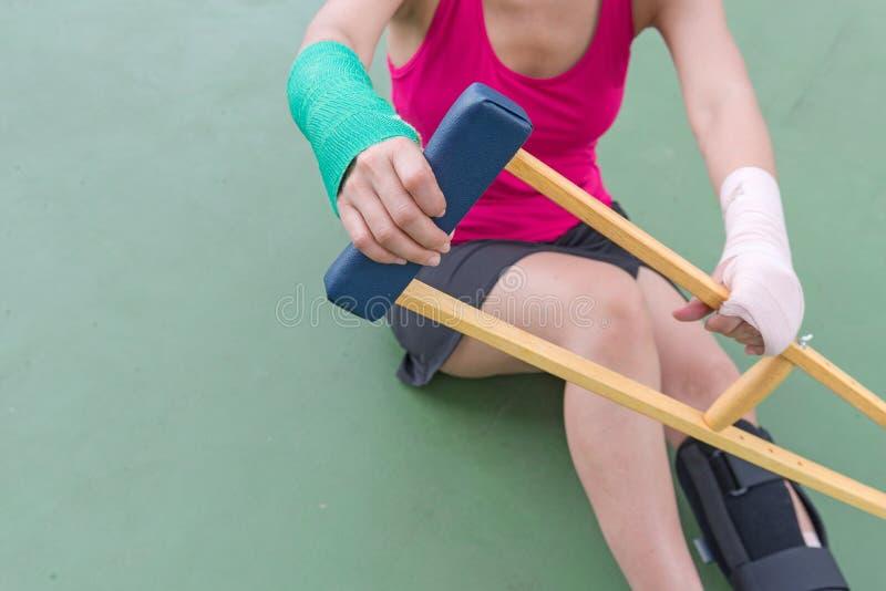 Γυναίκα τραυματισμών που φορά sportswear τον επίπονους βραχίονα και το πόδι με τη γάζα στοκ εικόνες