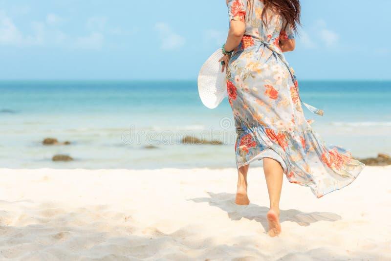 Γυναίκα τρόπου ζωής που φορά το καλοκαίρι φορεμάτων μόδας που τρέχει στην αμμώδη ωκεάνια παραλία Η ευτυχής γυναίκα απολαμβάνει κα στοκ φωτογραφία με δικαίωμα ελεύθερης χρήσης