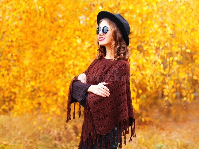 Γυναίκα φθινοπώρου μόδας που φορά ένα μαύρο στρογγυλό καπέλο και πλεκτό poncho στοκ εικόνα