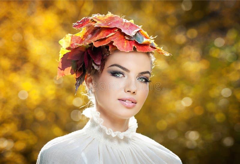 Γυναίκα φθινοπώρου. Όμορφο δημιουργικό ύφος makeup και τρίχας στον υπαίθριο βλαστό. Το πρότυπο κορίτσι μόδας ομορφιάς με φθινοπωρι στοκ εικόνα