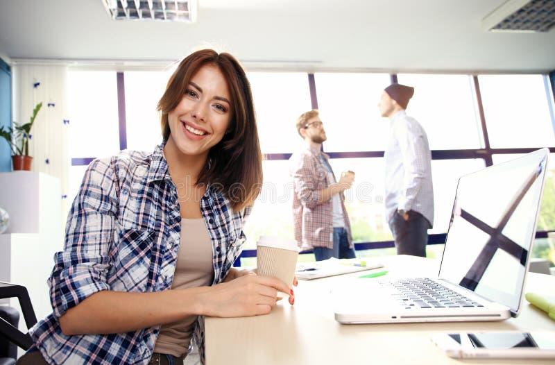 Γυναίκα φωτογραφιών που εργάζεται με το νέο πρόγραμμα ξεκινήματος στη σύγχρονη σοφίτα Γενικό σημειωματάριο σχεδίου στον ξύλινο πί στοκ εικόνα