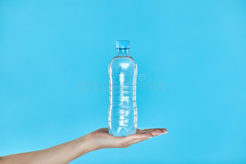 Γυναίκα χέρια κρατώντας ένα μπουκάλι νερό σε μπλε φόντο στοκ φωτογραφία με δικαίωμα ελεύθερης χρήσης