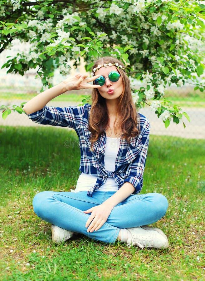 Γυναίκα χίπηδων μόδας που έχει τη διασκέδαση στη χλόη στον ανθίζοντας κήπο στοκ εικόνες