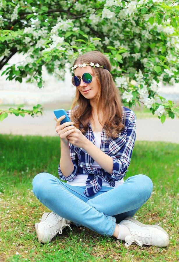 Γυναίκα χίπηδων που χρησιμοποιεί τη συνεδρίαση smartphone στη χλόη στον ανθίζοντας κήπο στοκ φωτογραφία