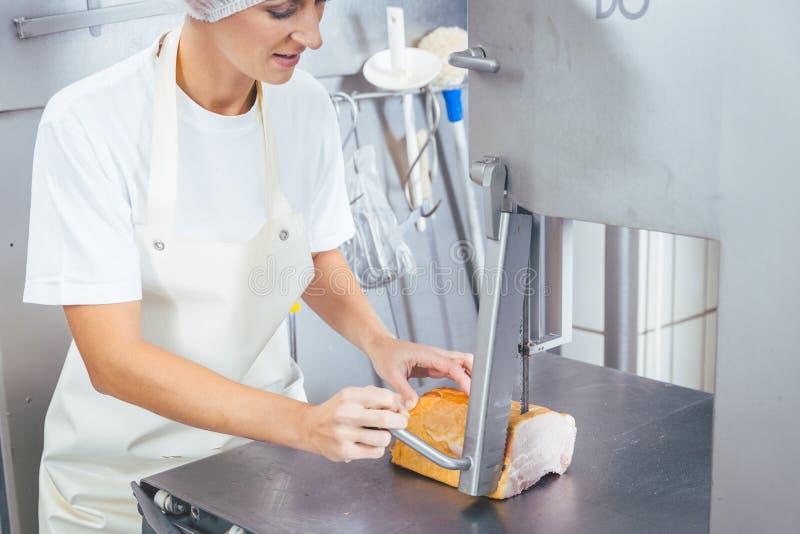 Γυναίκα χασάπηδων που χρησιμοποιεί το πριόνι για να κόψει το κρέας στο κρεοπωλείο της στοκ φωτογραφίες