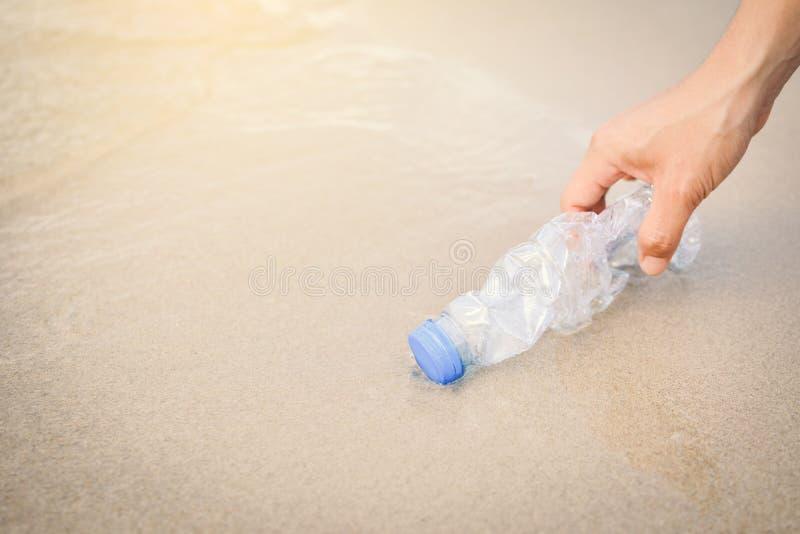 Γυναίκα χεριών που παίρνει τον πλαστικό καθαρισμό μπουκαλιών στην παραλία στοκ φωτογραφία με δικαίωμα ελεύθερης χρήσης