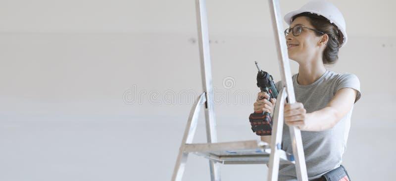 Γυναίκα χρησιμοποιώντας ένα τρυπάνι και εργαζόμενος στο καινούργιο σπίτι της στοκ φωτογραφία με δικαίωμα ελεύθερης χρήσης