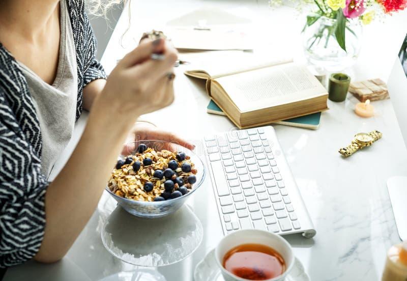 Γυναίκα χρησιμοποιώντας τον υπολογιστή και έχοντας τα δημητριακά στοκ εικόνες με δικαίωμα ελεύθερης χρήσης
