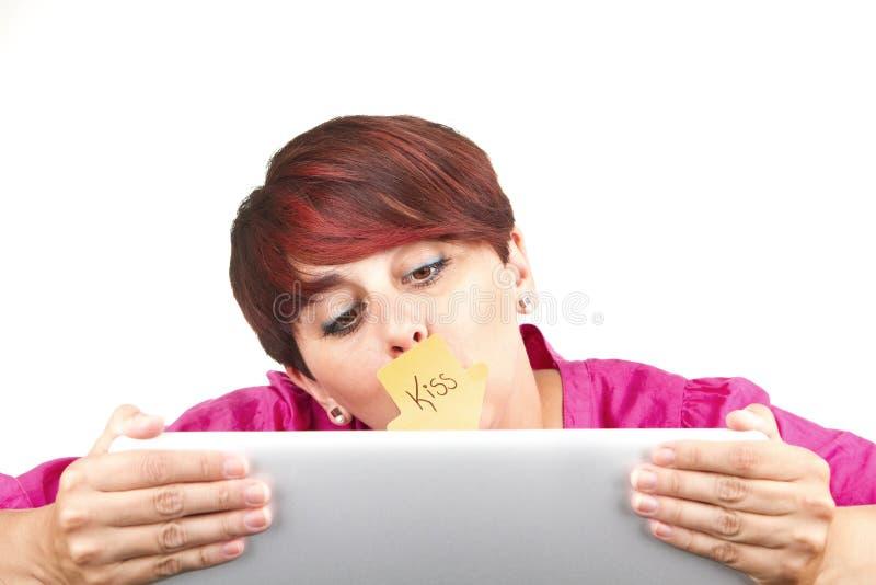 Γυναίκα χρησιμοποιώντας το lap-top και φιλώντας την οθόνη στοκ εικόνες